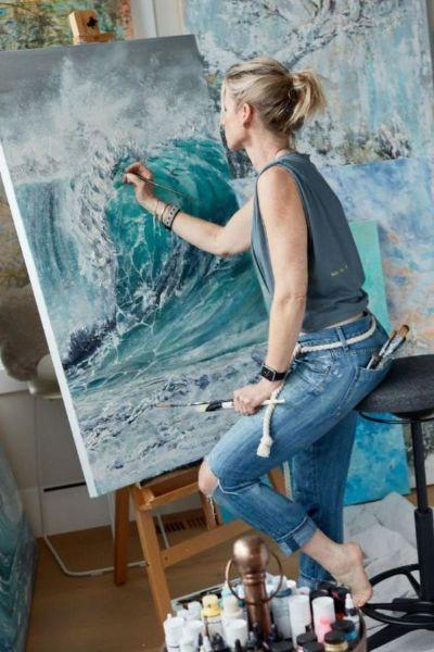 Artist Nikki Baxendale painting in her studio