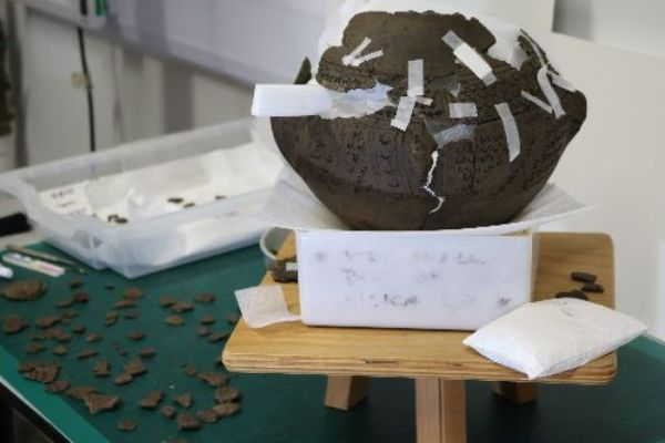 cremation urn in fragments partially held together with tape