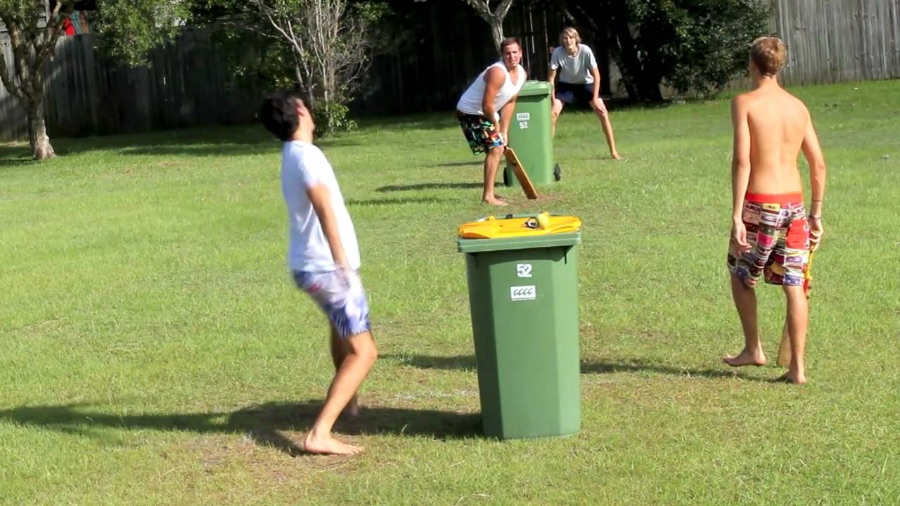 Image of a group of boys playing backyard cricket with wheelie bins and stumps