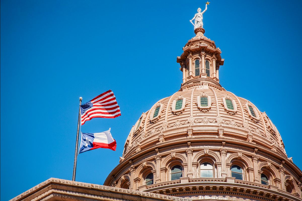 U.S. and Texas flags waving at the top of the Texas State Capitol