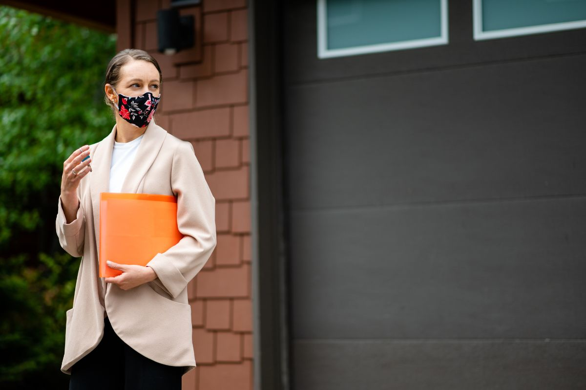A female real estate sales agent wearing a patterned face mask holds an orange file folder