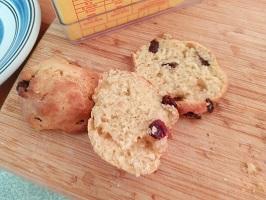 Two scones on a breadboard, one cut in half