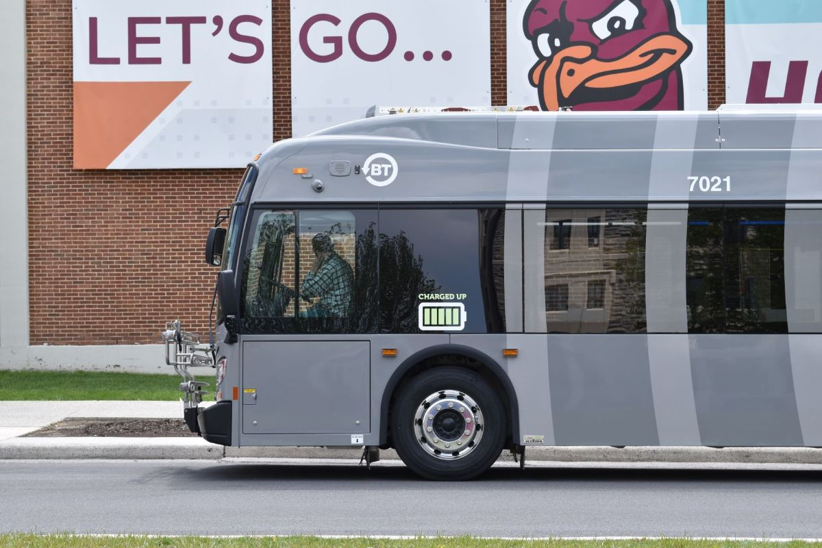 """Gray electric Blacksburg Transit bus is parked on the street in front of a """"Let's go Hokies"""" sign"""