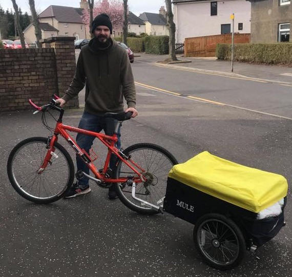 EATS Rosyth Project Support Assistant Ethan with his delivery bike and trolley.
