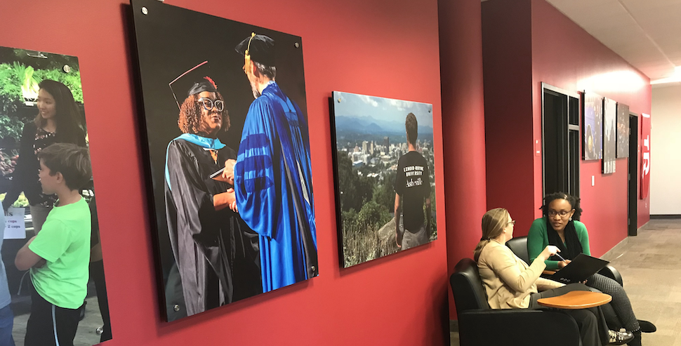 Two female students seated and talking next to red wall with graduation photos