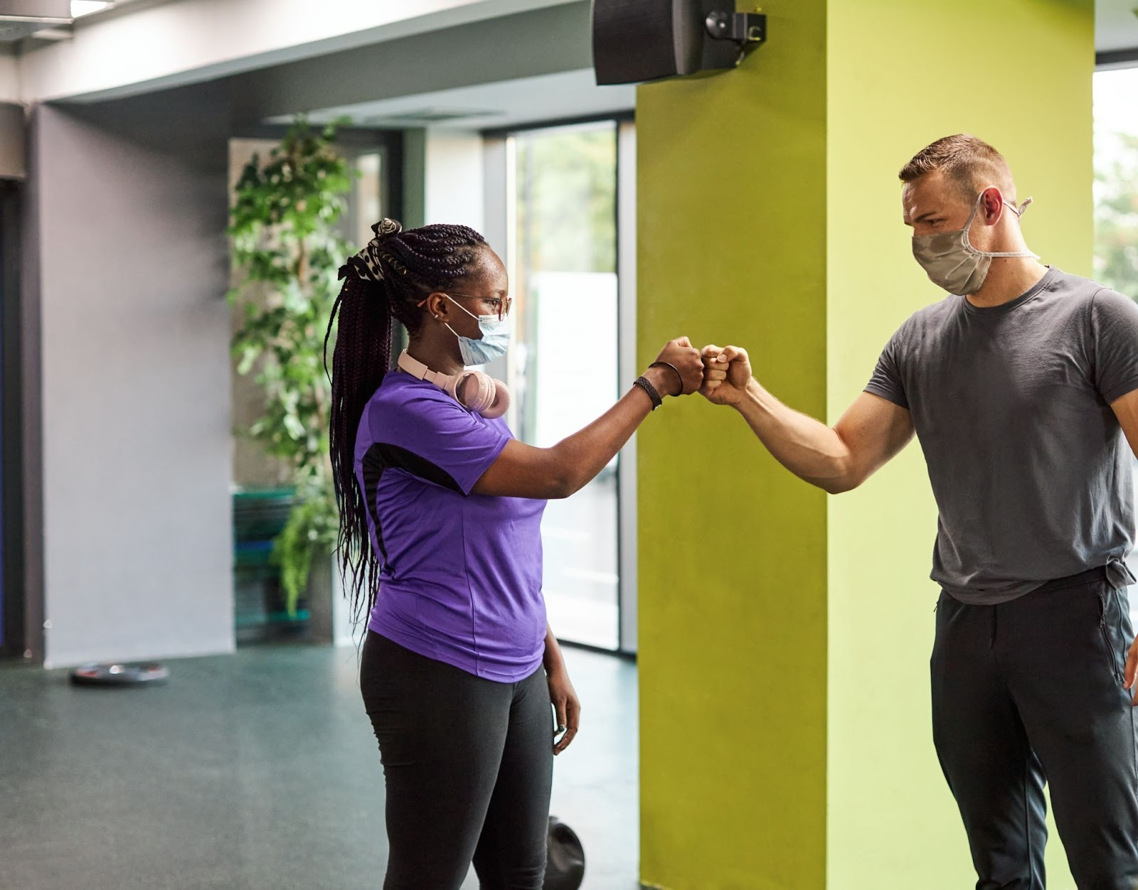 Woman and man doing a fist bump during a workout at the YMCA