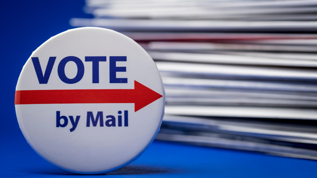 """A picutre of a button sitting in front of a stack of absentee ballot envelopes. The button has a red arrow pointing to the right and says """"Vote by Mail"""""""
