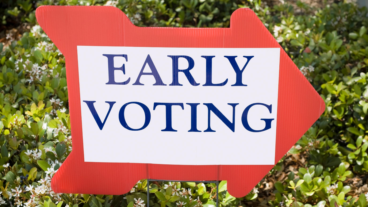 """A picture of a red arrow sign pointing right in front of some green bushes. On the red arrow, another white rectangular sign has been glued on top that says """"Early Voting""""."""
