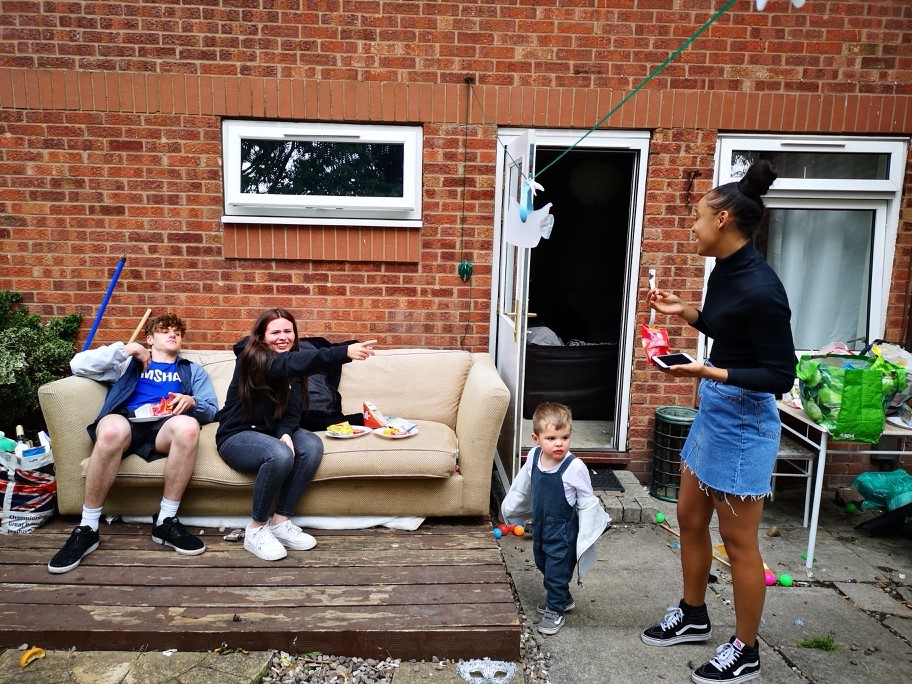 Young people outside with their children