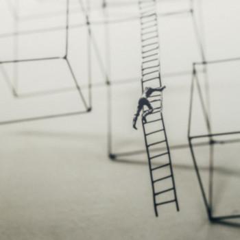 Symbolbild: Kletternde Person auf Leiter; Bild: Jason Wong/ unsplash.com.