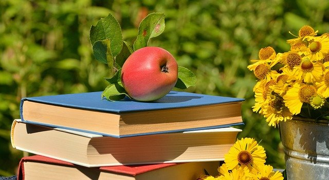 Summer reading books with an apple and flowers
