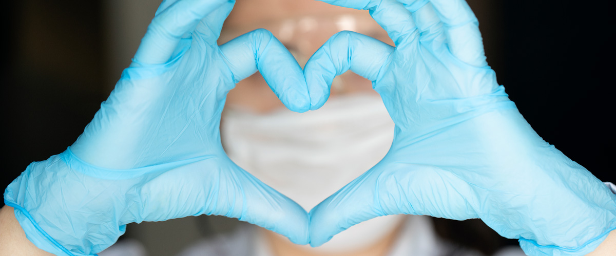 Photo of a healthcare worker, in mask and gloves, making a heart shape with their hands
