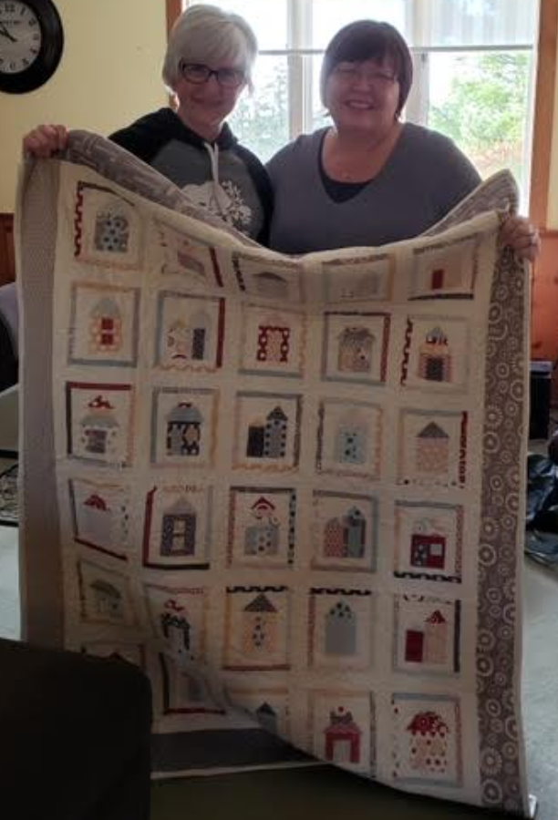 Heather Fisher and her friend holding a quilt with images of houses.