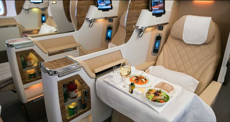 Premium meal with wine glass on a tray table in Emirates business class.