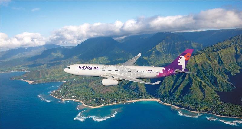 Hawaiian Airlines plane flying along coastline of Hawaii.
