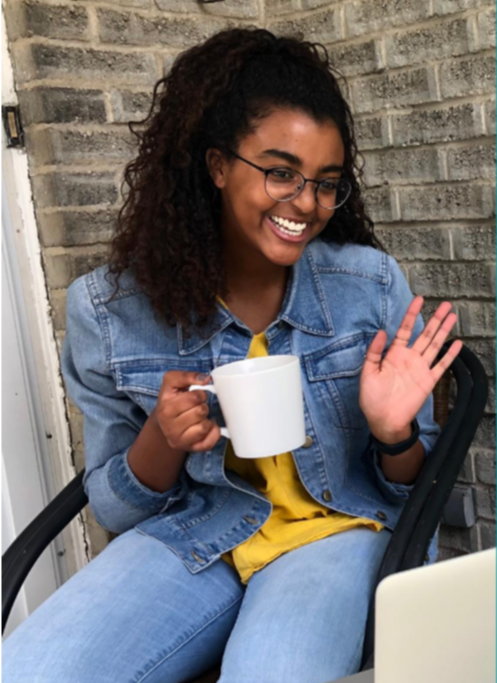 Student holding a coffee mug and waving