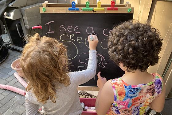 Kids focused on a chalk board