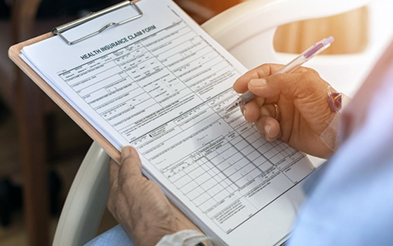 Person filling out health insurance form