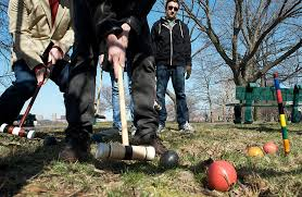 A close-up of men in black hoodies playing croquet