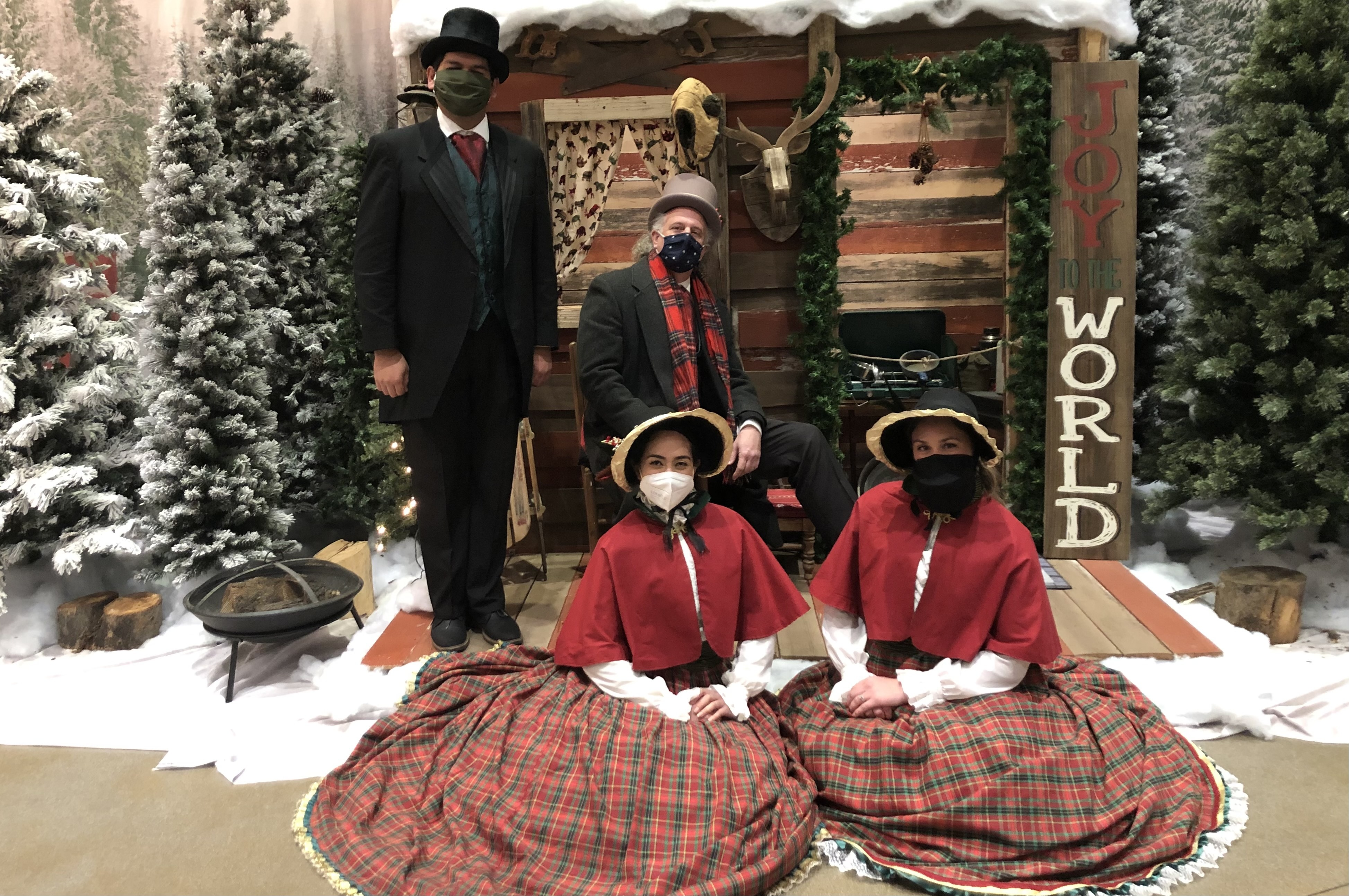 Carolers wearing traditional victorian garb and masks, posed in front of a scenic holiday winterland