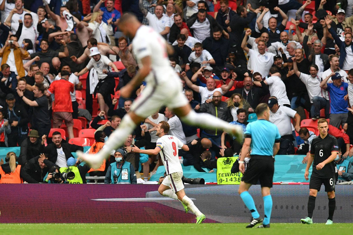 An English footballer leaps in the air. In the background fans go wild.