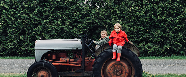 Two Kids Play on an Old Tractor