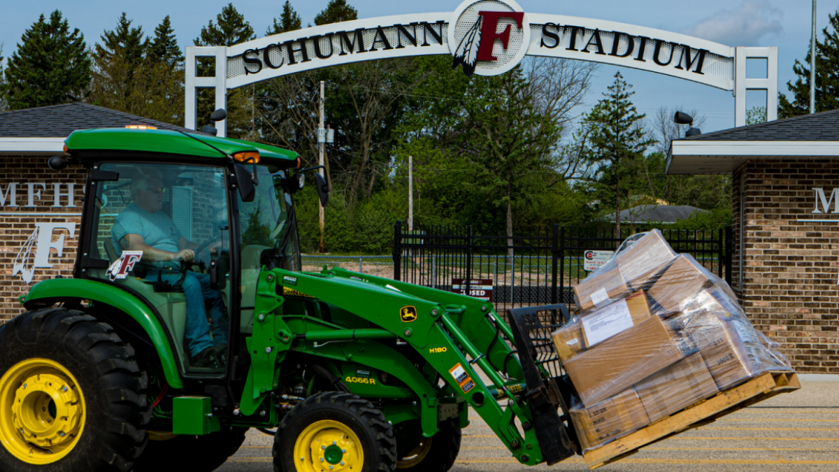 Pix of Green tractor delivering a pile of boxes.