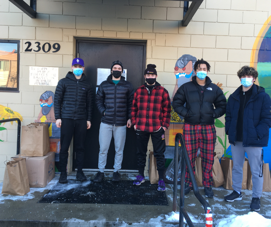 Five Cretin-Derham Hall students stand at the back entrance to the St. Stephen's office, surrounded by paper grocery bags full of supplies.