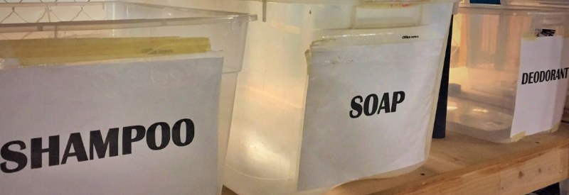 Three clear bins sit on the Donation Center shelves, with paper labels for shampoo, soap, and deodorant.