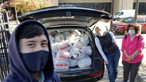 Community Engagement Coordinator Noah takes a selfie with a trunk full of to-go meals, and two other people involved in the project.