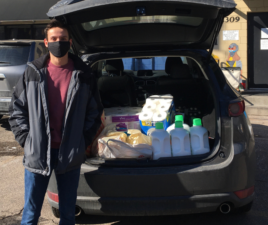 A Gravie representative stands in front of a car trunk filled with paper towels and cleaning supplies.