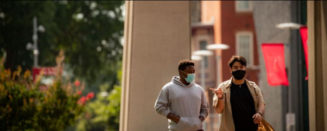 Stock photo of students wearing masks walking through campus