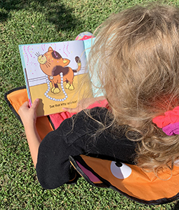 toddler sitting on grass reading book