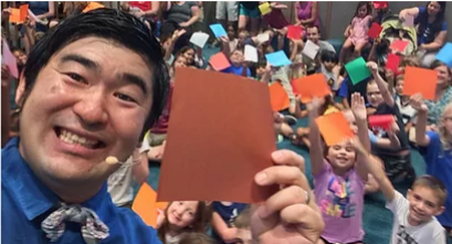 performer and room full of children smiling & holding origami paper