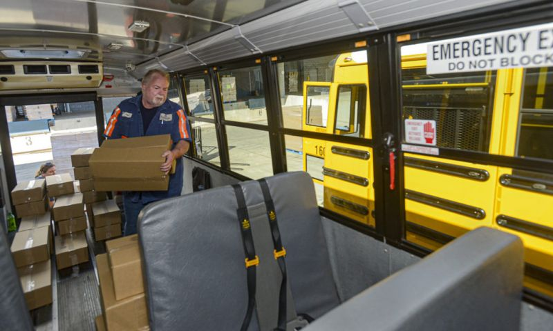 man loading packages on a school bus