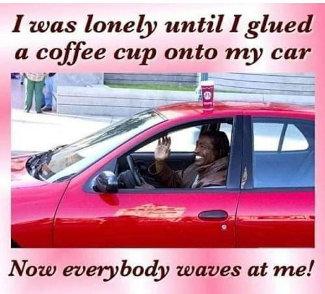 photo of a man smiling and waving while driving with a coffee cup on the roof of his car