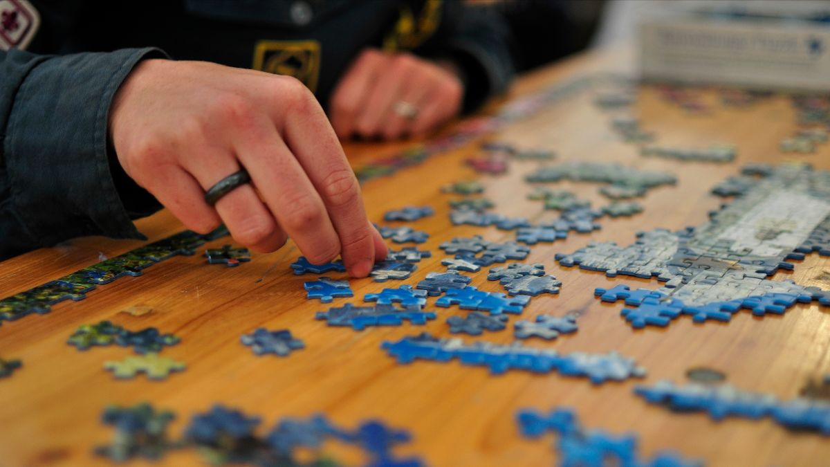 man working on jigsaw puzzle