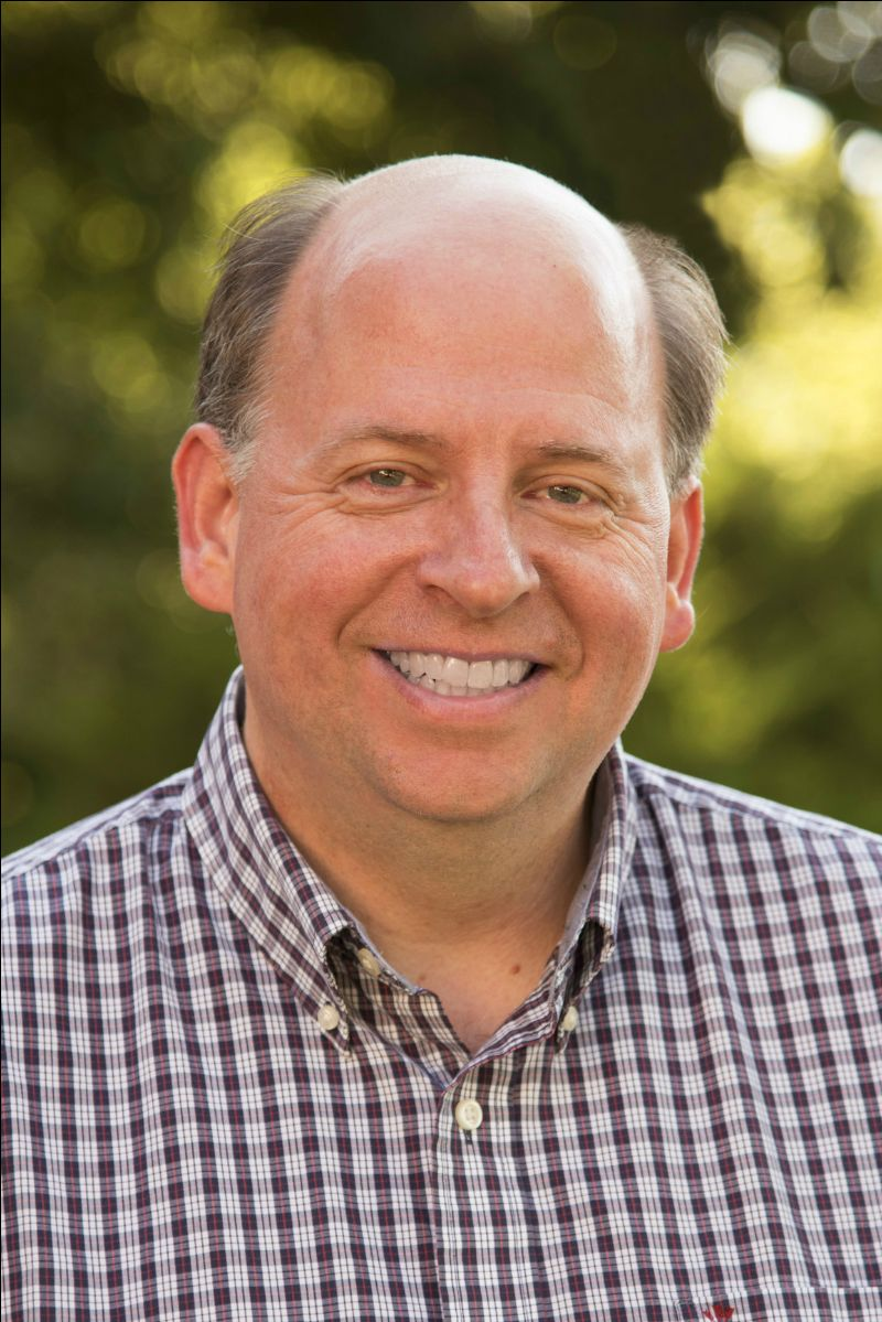 [Image Description: Photo of Jeff Hall. He is smiling with his teeth. He has green eyes, and dark hair with graying at his temples. He is balding, and wearing a plaid button up shirt. End image description.]