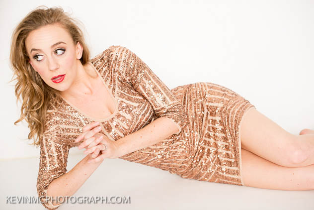 [Image Description: Photo of Whitney Kaufman. She is laying on her right side, with her right elbow propping her up. She is wearing a dress with champagne colored sequins arranged in varying striped patterns. He blonde hair is hanging down her back, and she is wearing bright red lipstick. She is looking off to the left, and facing the camera. End image description.]