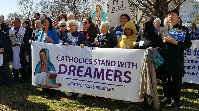 """Image of crowd with banner """"Catholics Stand With Dreamers"""""""