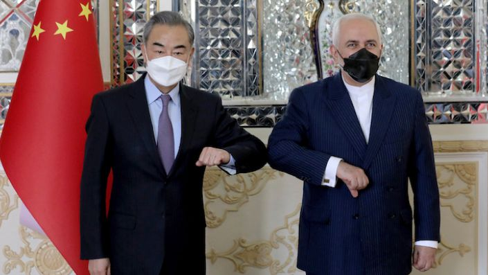 Iranian Foreign Minister Mohammad Javad Zarif, right, and his Chinese counterpart Wang Yi, pose for photos at the start of their meeting in Tehran, Iran, March 27. (AP Photo/Ebrahim Noroozi)