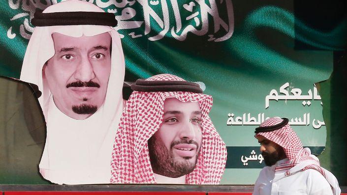 A man walks past a banner showing Saudi King Salman bin Abdulaziz, left, and Crown Prince Mohammed bin Salman, Jeddah, Saudi Arabia, Nov. 12, 2019. (AP Photo/Amr Nabil)