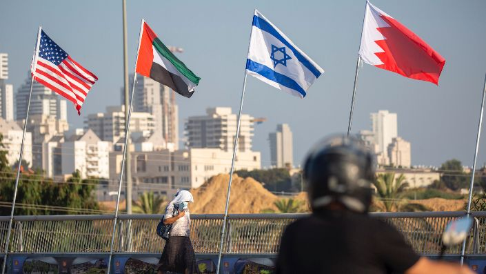 A woman wearing a face mask walks past flags for the United States, the United Arab Emirates, Israel, and Bahrain in Netanya, Israel, Sept. 14. (AP Photo/Ariel Schalit)