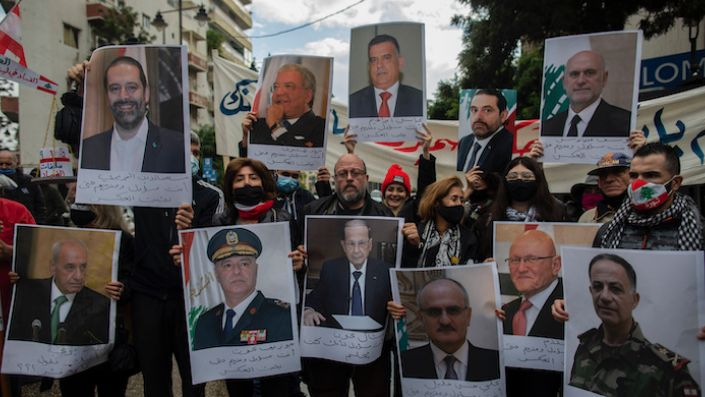 Anti-government protesters hold pictures of Lebanese leaders during a protest, in Beirut's Ashrafieh district, Lebanon, Nov. 26, 2020. (AP Photo/Hassan Ammar)