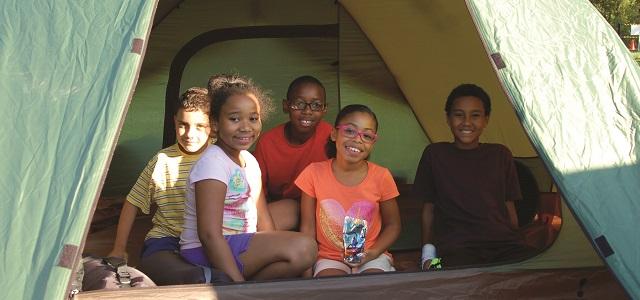 Kids sitting inside a tent