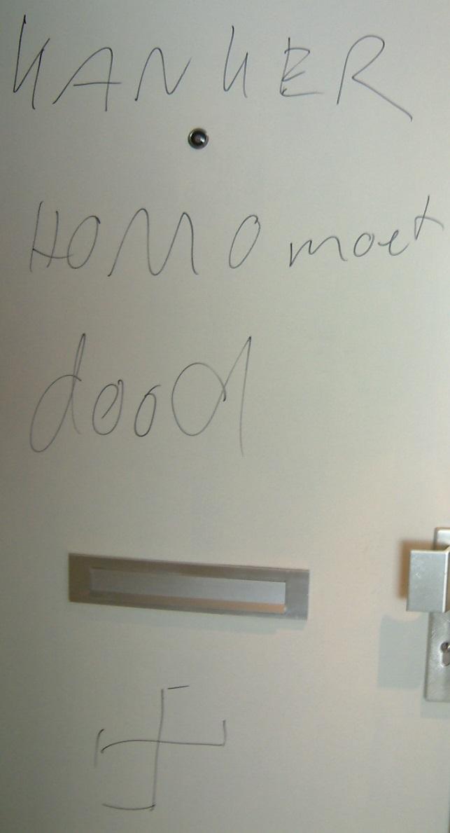 """Bekladde deur met tekst """"Kanker homo moet dood"""" en daaronder een hakenkruis"""