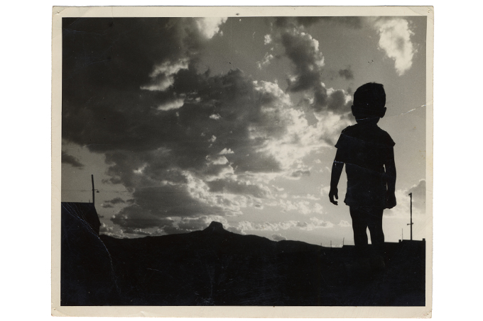 A little boy silhouetted against a skyline.