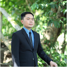Julius wearing a suit in front of trees