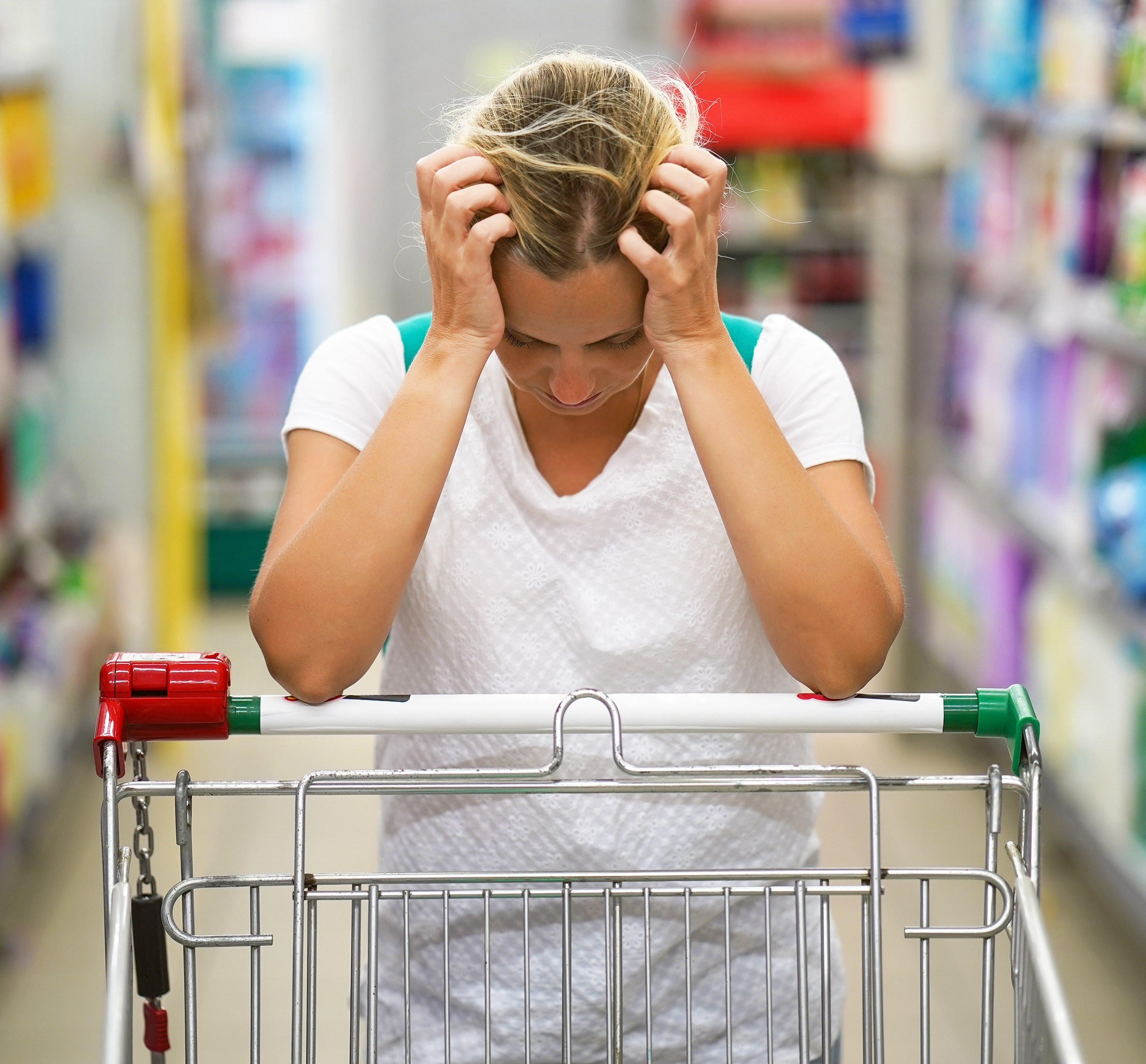 A young woman in a supermarket and leaning on an supermarket trolley and holding her head in her hands as if she is upset