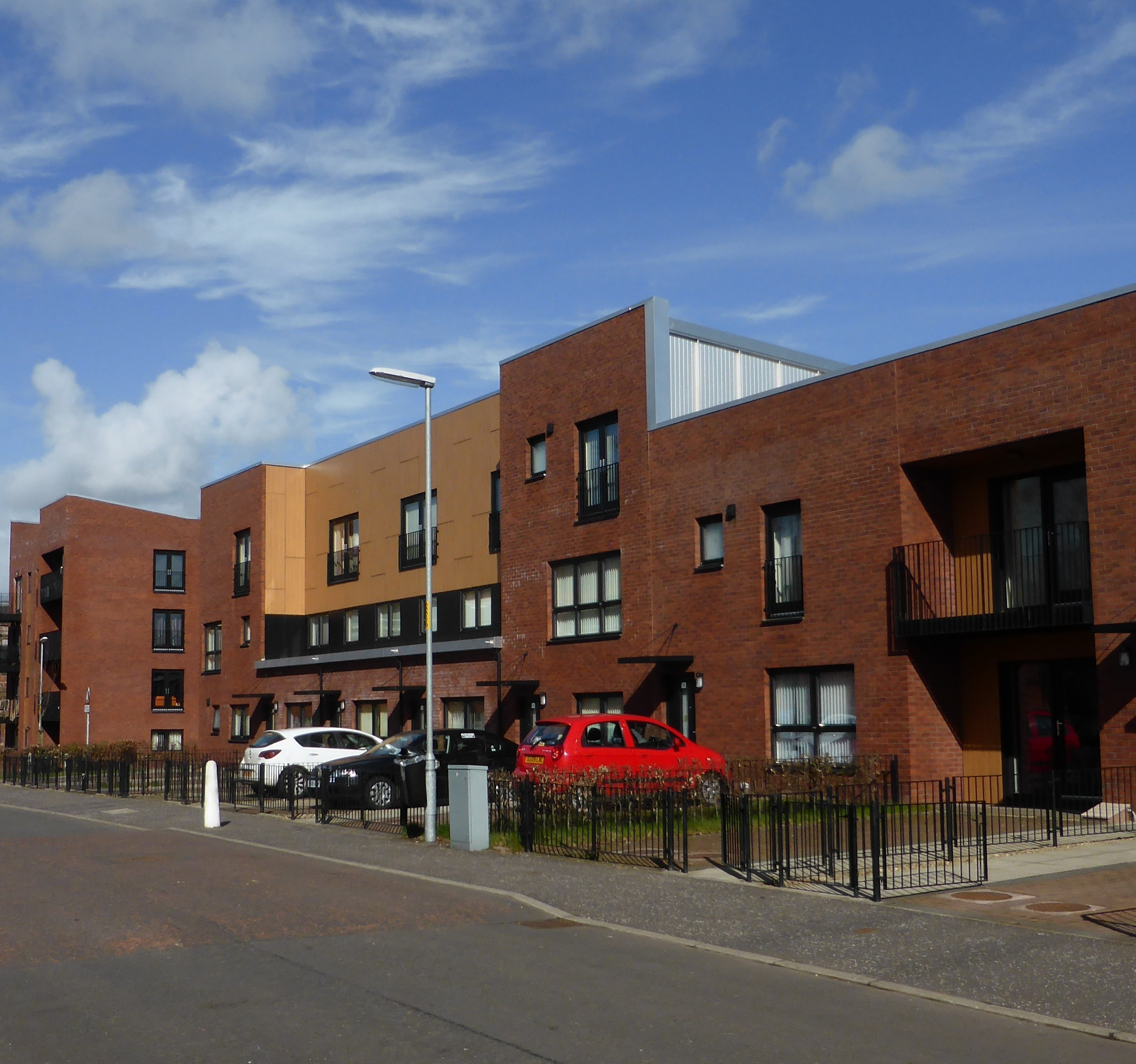 Road with blocks of flats in red brick with railings and cars outside